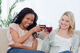 Two women holding wine glasses are smiling at the camera