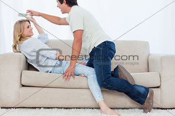 A man tries to get the television remote control off his girlfri
