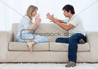 A couple sitting on a couch are having an argument