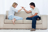 A couple sitting on a couch are pointing at each other