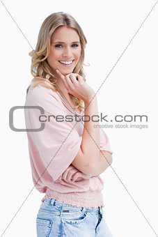 Smiling woman is resting her chin on her hand