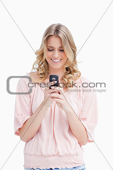 A smiling woman looking at her mobile phone