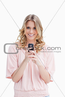 A woman holding a mobile phone is looking at the camera