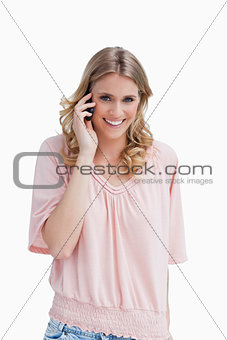 A woman smiling at the camera has her mobile phone up to her ear