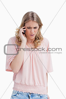 An angry woman is talking on her mobile phone