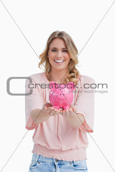 A smiling woman is holding a piggy bank in the palms of her hand