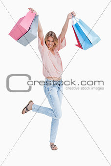 A woman is standing holding up shopping bags