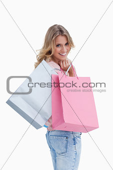 A woman looking back at the camera is carrying shopping bags ove