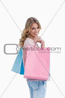 A woman carrying shopping bags is smiling at the camera