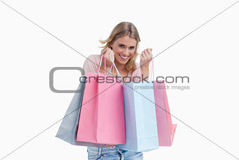 A smiling woman is carrying shopping bags