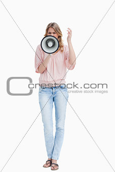 Front view of a young woman shouting with a megaphone