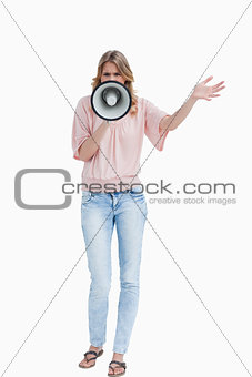 Young woman standing upright while using a megaphone