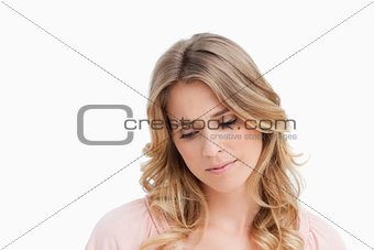 Calm young blonde woman looking down