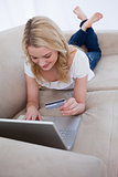 A woman lying on a couch is holding her bank card and typing on 