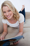 A smiling woman is lying on a couch and holding a magazine