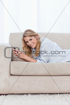 A woman smiling at the camera is holding a mobile phone
