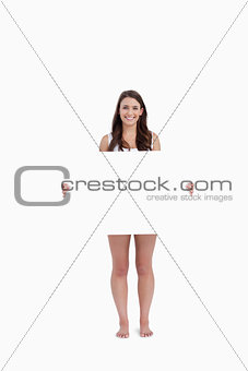 Smiling brunette holding a blank poster