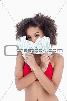 Brunette woman hiding her face behind two fans of notes