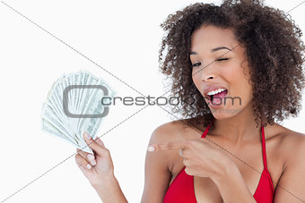 Young woman blinking an eye while holding a fan of notes