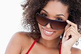 Smiling young brunette looking over her sunglasses
