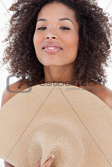 Attractive brunette woman hiding her body behind a hat