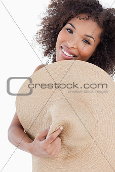 Young woman hiding her body behind a straw hat