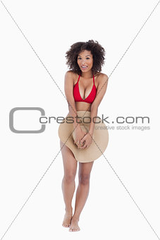 Smiling brunette woman standing upright while hiding herself