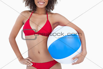 Smiling brunette woman holding a beach ball