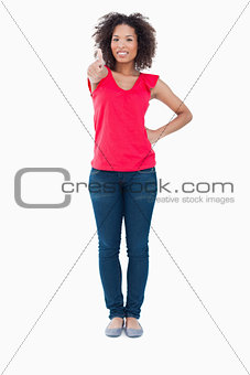 Smiling young brunette woman putting her thumbs up