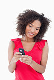 Smiling young brunette woman holding a mobile phone
