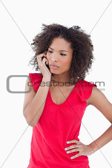 Serious brunette woman using her mobile phone