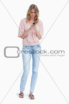 An angry woman standing looking at her mobile phone