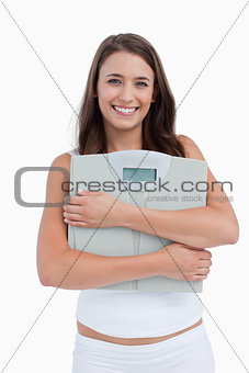 Smiling woman holding weighing scales