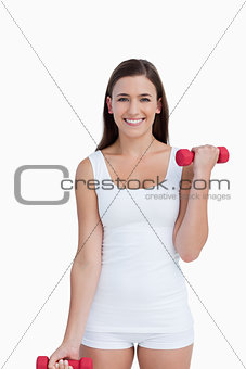 Attractive brunette holding red dumbbells