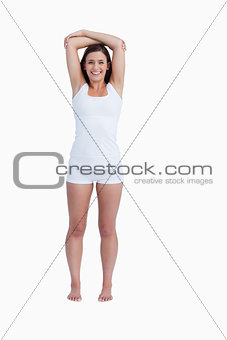 Smiling woman crossing her arms above her head