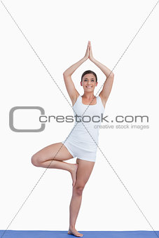 Smiling brunette woman practicing yoga