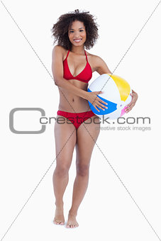 Smiling brunette holding a beach ball while standing upright