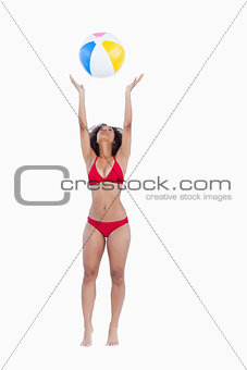 Attractive woman in bikini throwing a beach ball