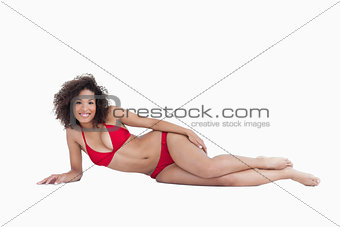 Smiling brunette lying down while looking at the camera