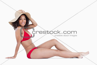 Attractive woman sitting down while holding her hat