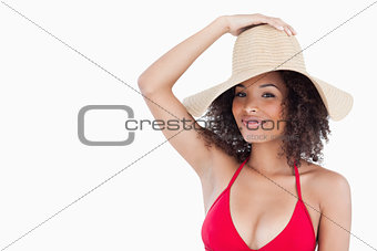 Attractive brunette woman in swimsuit holding her straw hat