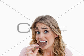 Young blonde woman looking at the camera while eating chocolate