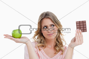 Young woman looking at a piece of chocolate while holding an app