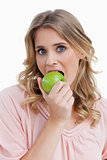 Young blonde woman eating an apple