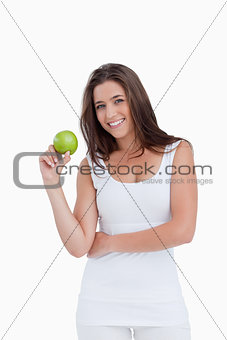 Smiling brunette woman holding a green apple