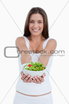 Bowl of salad being held by a young woman