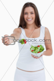 Fork with salad being held by a young woman