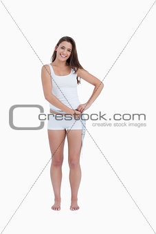 Smiling woman measuring her waist