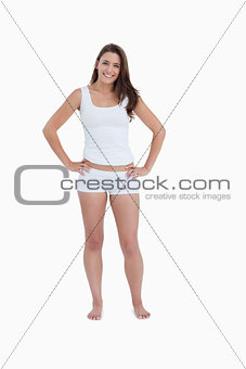 Smiling woman standing upright with her hands on her hips