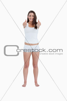 Smiling brunette woman placing her thumbs up